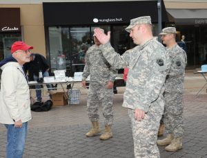 A Rotarian, left, in a red cap and white jacket, talks with 3 military people.